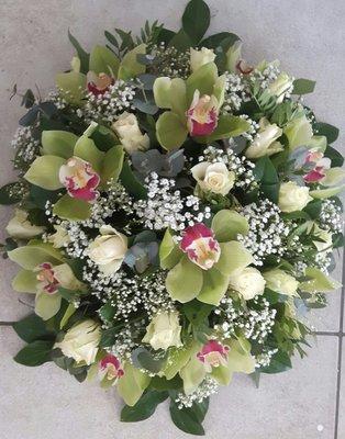 Rouwarrangement groene orchideeên en rozen